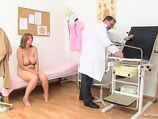 Doctor explores wide-opened pussy of a sexy cougar with huge tits