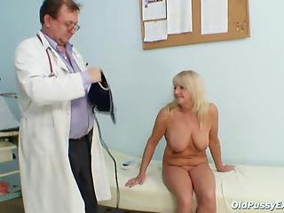 Perverted doctor shows a wide-opened pussy of a busty mature blonde