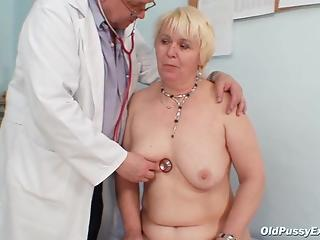 Gynecologist examines mature patient's pussy with special tool