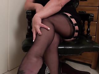 Mature hottie in black stockings stimulates her shaved pussy