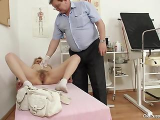 Fat doctor gently examines hairy pussy of mature blonde