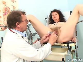 Old gynecologist carefully examines hairy pussy of mature patient