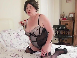 Mature in lingerie plays with striped dildo before sex