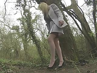 Lusty mature blondie is standing on the knees in the forest and sucking a dick