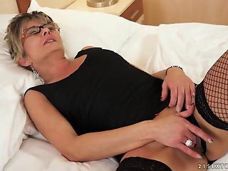 Busty mature lady sticks a huge transparent dildo in a tight pussy