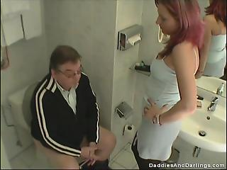 MILF with dyed hair blows an old fuck on the toilet